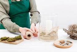 Florist at work: woman shows how to make natural, simple home decoration with glass candle holder decorated with moss and stones. Step by step, tutorial.