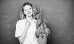 Florist concept. Botany and biology lesson. Botanical expert. Woman chalkboard background carry plant in pot. Take good care plants. Botany education. Botany is about plants flowers and herbs.