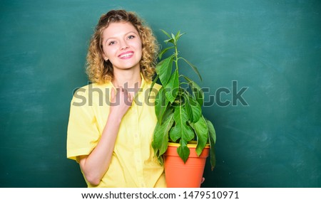 Florist concept. Botany and biology lesson. Botanical expert. Woman chalkboard background carry plant in pot. Take good care plants. Botany education. Botany is about plants flowers and herbs. #1479510971