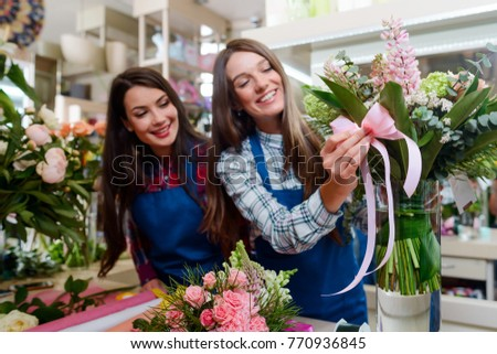 Florist decorates a bouquet with a pink bowknot. Fulfillment of an order, creating a gift for a birthday. Small floristry business.