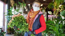 Florist employee in surgical mask protecting herself against COVID-19 coronavirus. Florist female looking into camera.