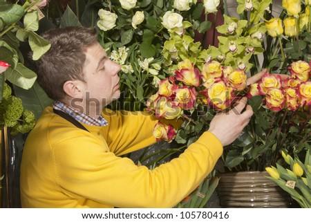 Florist finishing beautiful and rich flower arrangement