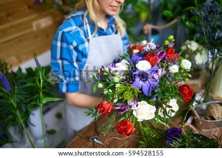 Florist holding fresh flowers to arrange into bouquet