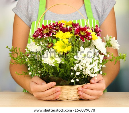 Florist makes flowers bouquet in wicker basket