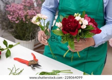 Florist making a bouquet. Selective focus on bouquet.