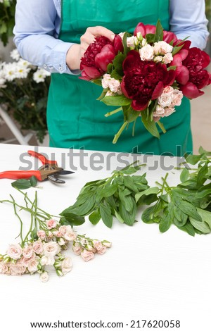 Florist making a red peonies and miniature roses bouquet. Selective focus on flowers.