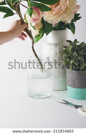 Florist placing cut flowers into a glass vase on white background #311854883