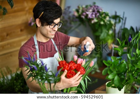 Florist refreshing red tulips in flower-shop #594529601