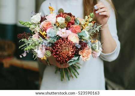 Florist shop in daylight. Woman holding beautiful bouquet of flowers. Florist with her work. Stylized tender photo with hipster filter.  #523590163