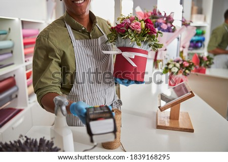 Florist shop manager giving a card-scanning machine to a client while holding a ribbon-wrapped pot in his hand