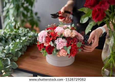 Florist woman creates flower arrangement in a round box. Beautiful bouquet of mixed flowers. Floral shop concept . Handsome fresh bunch. Flowers delivery Photo stock ©