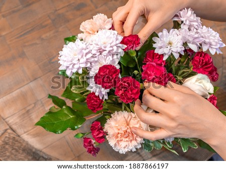 Florist woman hands making mix colorful fresh flowers with green leaves for a wedding celebration decor. Closeup bunch of beautiful blossom floral, top view. Decoration specialist concept. Valentines. Foto stock ©