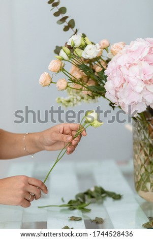 Florist work: pretty young woman making a trendy modern bouquet of different flowers. Florist collects a bouquet. Creating bouquets and flower arrangements. Small business florist.