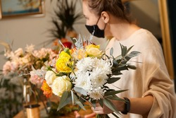Florist works with colors. Flower seller chooses flowers for future bouquet. Flowers shop worker in a mask standing in flower shop and checking flowers in glass vase.
