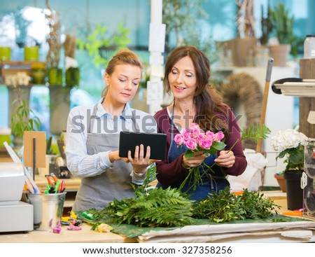 Florists using digital tablet while making bouquet of pink roses in flower shop
