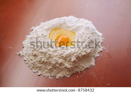 Flour and egg on wooden table