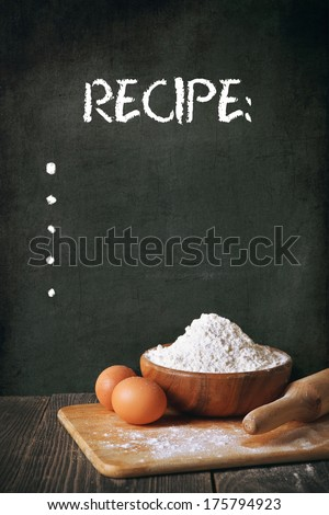 Flour and eggs on a blackboard background. space for recipe