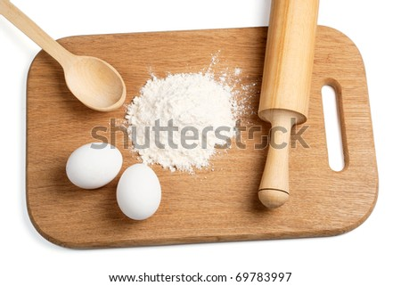Flour and eggs on a wooden board #69783997