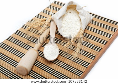 Flour and wheat grain with wooden spoon on a wooden table.