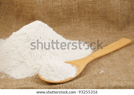 Flour and wooden spoon on jute hessian background