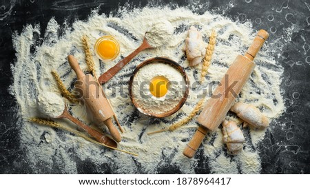 Flour, eggs, and rolling pin, Preparation of dough. Bakery on a black stone background. Top view. Free space for text. Stock photo ©