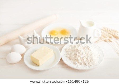 flour, eggs, butter and milk on a white wooden background, ingredients for baking