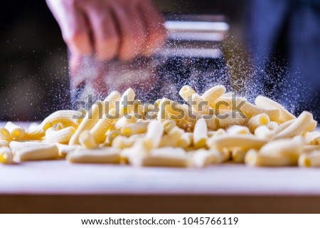 Flour falling over pasta. Falling penne pasta. Rigatoni pasta with flour powder particle falling. Rigatoni Penne Lisce Tortiglioni Doppia Rigatura. Home made rigatoni pasta on the table with flour.