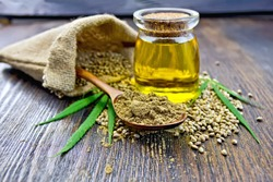 Flour hemp in a wooden spoon, seed in a bag and on the table, oil in a glass jar, cannabis leaves on the background of wooden boards