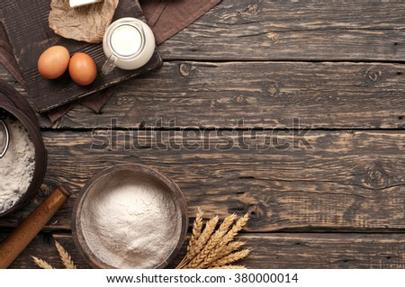 flour in a wooden bowl on dark wooden background with spikelets of wheat, eggs and milk, top view with copy space