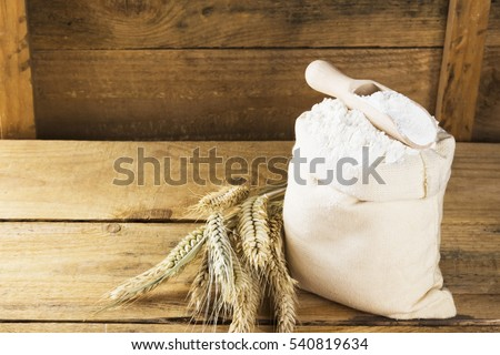Flour in bag and wheat ears on a wooden background. Copy space. Food background.