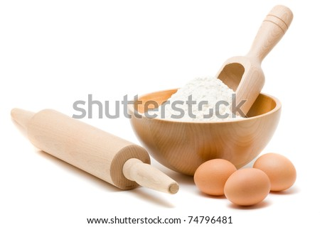 Flour in bowl with eggs and rolling pin over white background