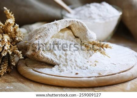 Flour in burlap bag on cutting board and wooden table background