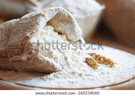 Flour in burlap bag on cutting board and wooden table background #260258060