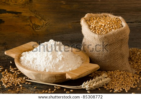 Flour in homemade wooden bowl and wheat in burlap bag