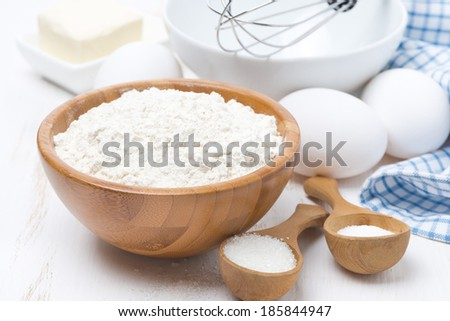 flour, salt, sugar and eggs for baking pancakes on wooden table, horizontal