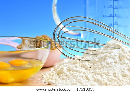 Flour, whisk and eggs in a bowl, baking ingredients