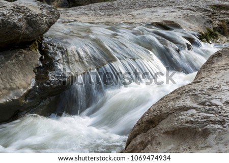 flow of the mountain river flows through the stone rapids, the water flows