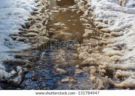 Flow of water with lumps snow melts on the road in the city