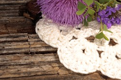 Flower and crochet doily on wood surface. Isolated closeup.