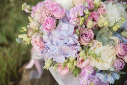 Flower arrangement in a purple hat box was created by a florist for a wedding gift. Flower bouquet of purple hydrangea, white freesia, pink ranunculus asiaticus, eustoma flowers, roses and eucalyptus