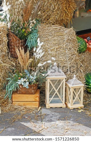 Flower arrangements and candlesticks stand near the hays as decoration at the market #1571226850