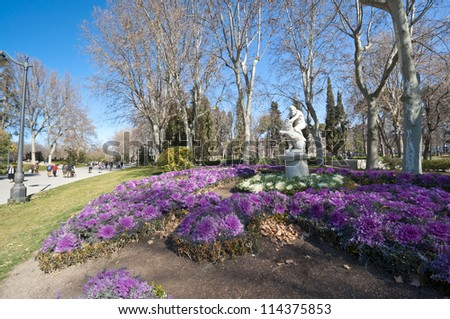 Flower bed at Retiro Park, Madrid, Spain. The statue depicts Hercules slaying Nemean lion.