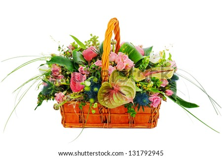 Flower bouquet arrangement centerpiece in a wicker gift basket isolated on white background.