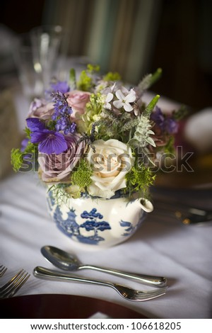 flower bouquet displayed in a teapot at a table setting