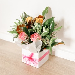 Flower bouquet in white box with pink ribbon. Wooden flooring. White wall behind. Pink flowers, green leaves. Side angle.