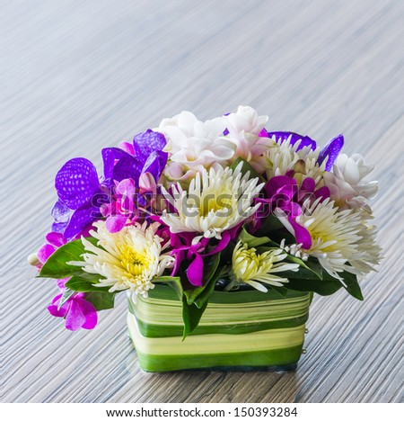 Flower bouquet of vanda, orchid, chrysanthemum on wood table