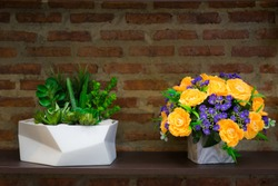 Flower bouquet with beautiful orange, purple flowers artificial and succulent cactus on wooden table and brick wall in background