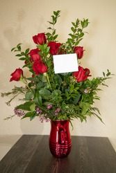 Flower bouquet  with one dozen red roses and wax flowers in a red vase with a blank card for text.