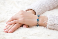 Flower bracelet on woman's hand wrist on white, fluffy fur blanket. Skin care and beauty in winter time. Closeup.