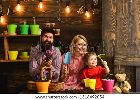 Flower care watering. Soil fertilizers. happy gardeners with spring flowers. woman, man and little boy child love nature. Family day. Greenhouse. Father and son with mother. Gentle work. #1316492054